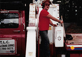 Man Standing In Front Of T.L.C Truck