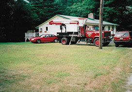 T.L.C. Tree& Crane Service Truck In Front Of House